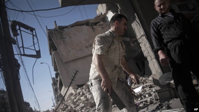 Syrian men salvage belongings from a destroyed buildings in the Bustan al-Qasr neighborhood of Aleppo, Syria, September 21, 2012.
