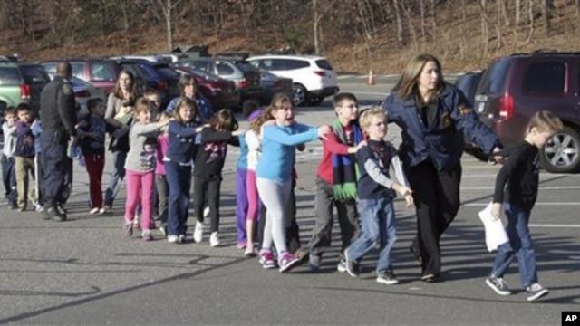 Anak-anak SD Sandy Hook di Newtown, Connecticut dibawa ke tempat aman oleh polisi setelah terjadi penembakan Jumat pagi