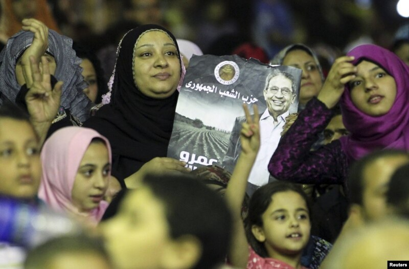 Supporters of presidential candidate and former Arab League secretary general Amr Moussa hold posters during a campaign rally in El-Kalubia, May 16, 2012.