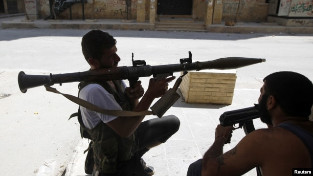 Free Syrian Army fighter waits for Syrian Army tanks to advance in the Salaheddin neighborhood in central Aleppo, Aug. 10, 2012.